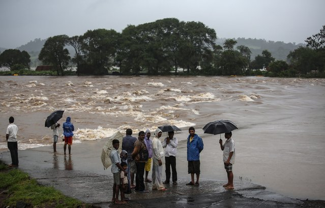 People stand on the side of the Sai River Vatika road as the Tansa River overflows due to heavy rain, near Vajreswari village around 70 kms from Mumbai, India, 29 July 2014. The India Meteorological Department (IMD) issued an alert of very heavy rainfall in Mumbai and the Konkan region over the next 24 hours. (Photo by Divyakant Solanki/EPA)