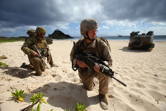 U.S. Marine Captain Jared Krogh (C) leads Australian Army soldiers from the 5th Battalion, Royal Australian Regiment up the beach after landing in amphibious assault vehicles from the USS Peleliu while participating in an assault exercise at Marine Corps Base Hawaii during the multi-national military exercise RIMPAC in Kaneohe, Hawaii, July 29, 2014. RIMPAC is a giant U.S.-led naval exercise involving 22 countries. (Photo by Hugh Gentry/Reuters)