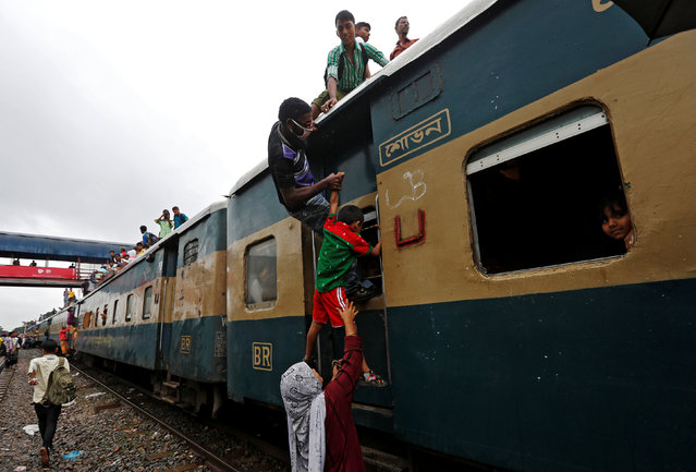 A couple helps their son to climb on top of an overcrowded passenger train as they travel home to celebrate Eid al-Fitr festival, which marks the end of the Muslim holy fasting month of Ramadan, at a railway station in Dhaka, Bangladesh, July 5, 2016. (Photo by Adnan Abidi/Reuters)
