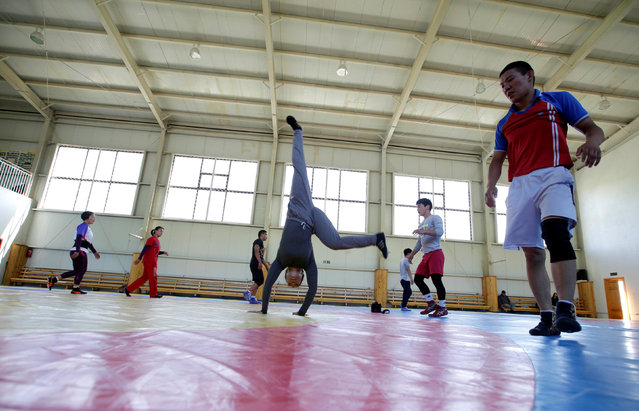 Mongolia's wrestler Oyuntuya Otgonbat (C) warms up ahead of a daily training session at the Mongolia Women's National Wrestling Team training centre in Bayanzurkh district of Ulaanbaatar, Mongolia, July 1, 2016. (Photo by Jason Lee/Reuters)