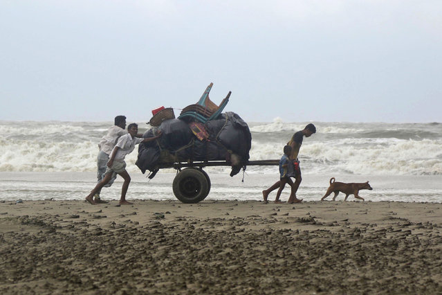 Bangladeshis push a cartload of belongings and walk homewards after spending a night at a shelter in Cox's Bazar, Bangladesh, Tuesday, May 30, 2017. A tropical storm lashed southern Bangladesh on Tuesday, destroying hundreds of poorly built homes in some remote islands in the Bay of Bengal, officials said. No casualties were immediately reported. (Photo by AP Photo/Stringer)