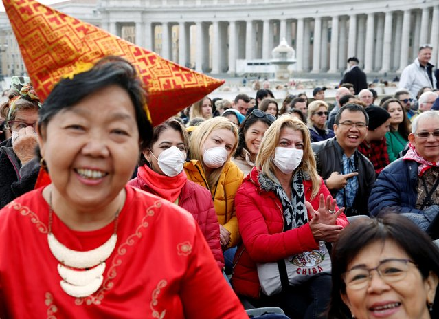 Faithful in face masks react as they wait for Pope Francis to arrive for the weekly general audience at the Vatican on February 26, 2020. (Photo by Remo Casilli/Reuters)