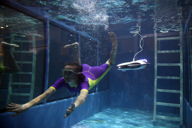 A product demonstrator dives with a underwater drone a day before the opening of the World Robot Conference held in Beijing, China, Tuesday, August 22, 2017. (Photo by Fu Ting/AP Photo)