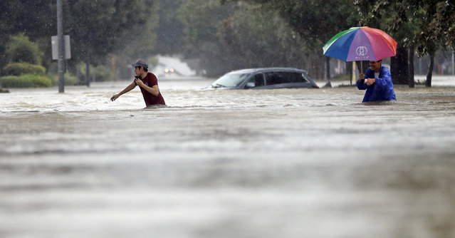Moses Juarez, left, and Anselmo Padilla wade through floodwaters from Tropical Storm Harvey on Sunday, August 27, 2017, in Houston, Texas. (Photo by David J. Phillip/AP Photo)