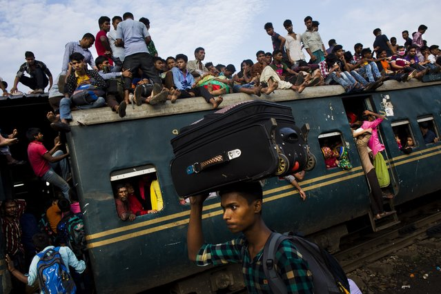 Bangladeshi Muslims travel on the roof of an overcrowded train as they head to their hometowns ahead of Eid al-Adha in Dhaka, Bangladesh, Friday, September 1, 2017. (Photo by Bernat Armangue/AP Photo)