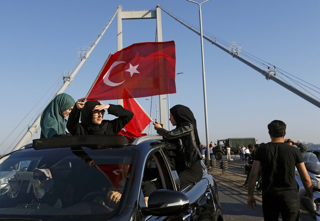 Women wave Turkish flags after troops involved in the coup surrendered on the Bosphorus Bridge in Istanbul, Turkey July 16, 2016. (Photo by Murad Sezer/Reuters)