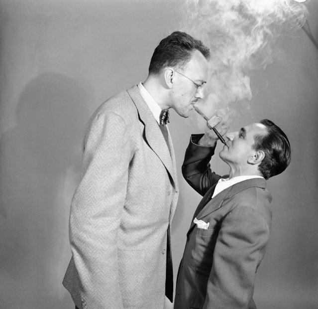 "George Braunsdorf, left, 6 feet 4 inches and Joe Damone, 5 feet 1 inch, demonstrate a pipe called the ""Double Ender"" in New York, June 2, 1949. According to its manufacturer, the pipe was designed as a means of conserving tobacco by a couple of pipe smokers down on their luck, or, sharing a smoke at a ball game. (Photo by Ed Ford/AP Photo)"