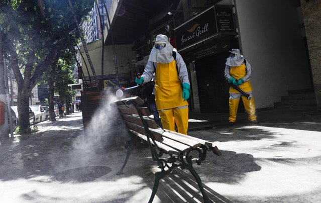 Cleaners disinfect the streets of Icarai neighbourhood during the coronavirus disease (COVID-19) outbreak in Niteroi near Rio de Janeiro state, Brazil, March 23, 2020. (Photo by Ricardo Moraes/Reuters)