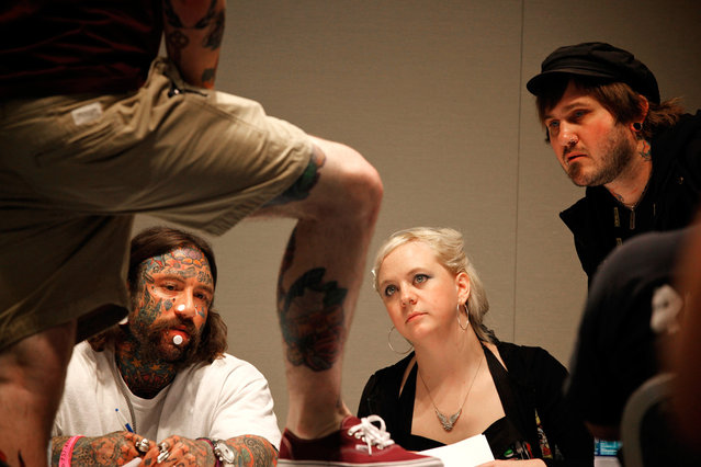 Tattoo judges inspect the tattoos of a competitor at the Hampton Roads Tattoo Festival in Virginia, on March 2, 2012. (Photo by Larry Downing/Reuters)