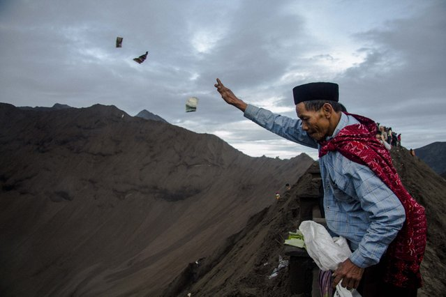 An Indonesian Tenggerese Hindu worshipper throws moneys as an offering towards the crater of Mount Bromo during the Yadnya Kasada Festival in Probolinggo, East Java, Indonesia, 21 July 2016. (Photo by Fully Handoko/EPA)