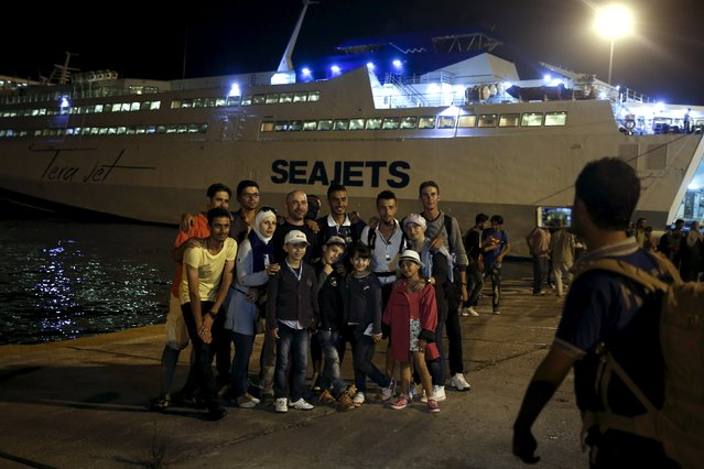 "A Syrian refugee family takes a picture in front of the passenger ship ""Tera Jet"", following their trip from the island of Lesbos to the port of Piraeus, near Athens, Greece September 1, 2015. (Photo by Alkis Konstantinidis/Reuters)"