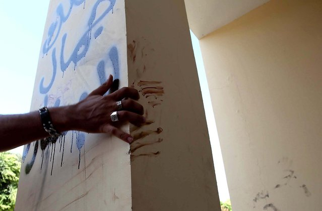 """A man explains that the bloodstains on the column are from one of the American staff members who grabbed the edge of the column while he was evacuated after the attack that killed four Americans, including Ambassador Chris Stevens, on Tuesday night in Benghazi. The Arabic writing on the column reads """"Villa of Jamal al Beshary"""", which was written by the owner to protect the property from another attack. (Photo by Mohammad Hannon/Associated Press)"""