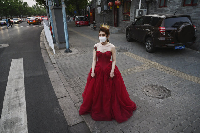 A Chinese woman wears her dress and a protective mask as she waits to change after taking pictures in advance of her wedding near the Forbidden City, on April 30, 2020 in Beijing, China. Beijing lowered its risk level after more than three months Thursday in advance of the May holiday, allowing most domestic travellers arriving in the city to do so without having to do 14 days of quarantine. The Forbidden City will open to a limited number of visitors as of Thursday morning. After decades of growth, officials said China's economy had shrunk in the latest quarter due to the impact of the coronavirus epidemic. The slump in the world's second largest economy is regarded as a sign of difficult times ahead for the global economy. While industrial sectors in China are showing signs of reviving production, a majority of private companies are operating at only 50% capacity, according to analysts. With the pandemic hitting hard across the world, officially the number of coronavirus cases in China is dwindling, ever since the government imposed sweeping measures to keep the disease from spreading. Officials believe the worst appears to be over in China, though there are concerns of another wave of infections as the government attempts to reboot the world's second largest economy. Since January, China has recorded more than 81,000 cases of COVID-19 and at least 3,200 deaths, mostly in and around the city of Wuhan, in central Hubei province, where the outbreak first started. (Photo by Kevin Frayer/Getty Images)