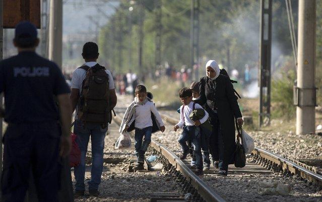 A migrant family tries to cross the Macedonian-Greek border near Gevgelija, Macedonia, as a Greek policeman looks at them, September 5, 2015. (Photo by Stoyan Nenov/Reuters)