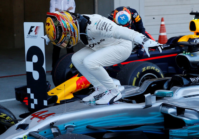 Mercedes' British driver Lewis Hamilton stands on his car in celebration of his victory after returning to the parc ferme in the Formula One Japanese Grand Prix at Suzuka on October 8, 2017. (Photo by Toru Hanai/Reuters)