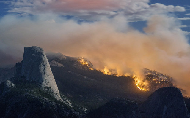 In this Sunday, September 7, 2014, photo provided by Michael Frye, a wildfire burns next to Half Dome in Yosemite National Park, Calif.  As of Monday, the fire has burned through about four square miles. (Photo by AP Photo/Michaelfrye.com)