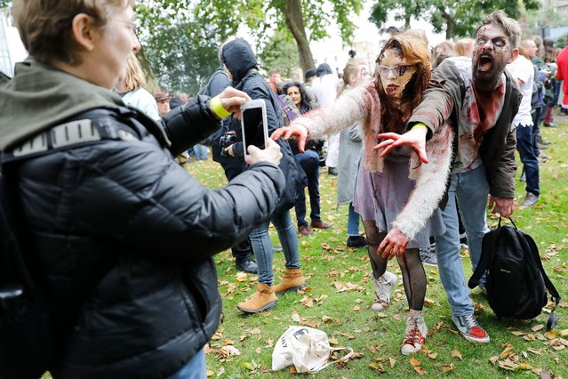 """People wearing costumes pose for a photograph as they gather before participating in a """"Zombie Walk"""" on World Zombie Day, in London on October 7, 2017. (Photo by Tolga Akmen/AFP Photo)"""