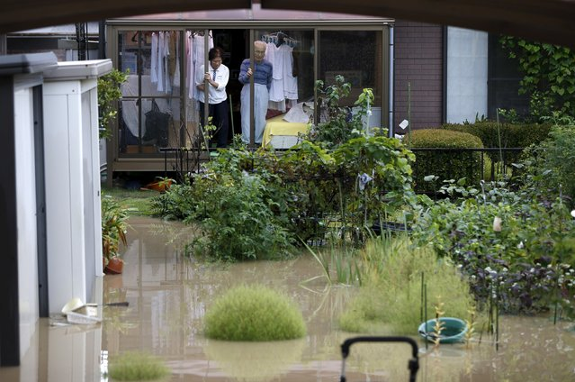 People look out from a house at a residential area flooded by the Kinugawa river, caused by typhoon Etau, in Joso, Ibaraki prefecture, Japan, September 10, 2015. (Photo by Issei Kato/Reuters)