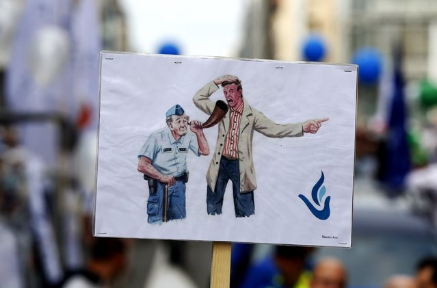 A Belgian policeman holds a placard showing a cartoon of an old police officer during a demonstration in central Brussels September 18, 2014. Several thousand policemen are demanding to keep their right to choose to retire before the age of 62. (Photo by Yves Herman/Reuters)