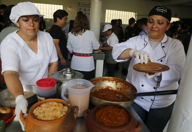 Mexican inmates Elizabeth (L) and Adriana cook traditional Mexican food during a culinary competition at the Santa Monica female prison in Lima, September 10, 2015. (Photo by Mariana Bazo/Reuters)