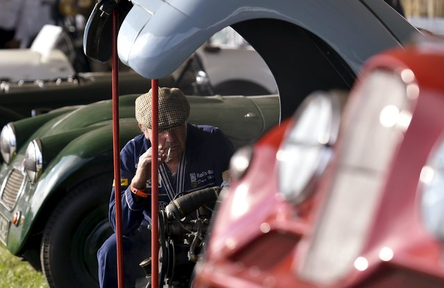 A man sits near the open engine of a vintage car at the Goodwood Revival historic motor racing festival in Goodwood, near Chichester in south England, Britain, September 11, 2015. (Photo by Toby Melville/Reuters)
