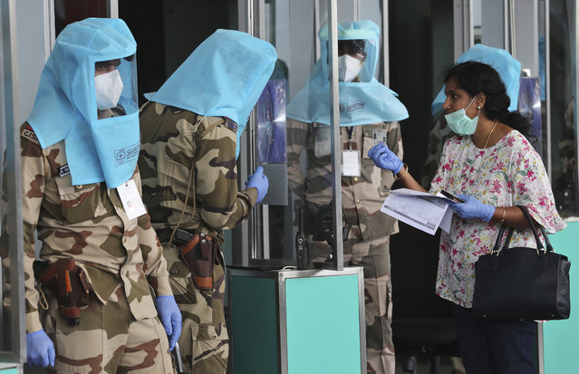 Indian security personnel wearing protective gear check the identity of a passenger through a glass before allowing her inside the departure terminal at Kempegowda International Airport in Bengaluru, India, Tuesday, June 2, 2020. More states opened up and crowds of commuters trickled onto the roads in many of India's cities on Monday as a three-phase plan to lift the nationwide coronavirus lockdown began despite an upward trend in new infections. (Photo by Aijaz Rahi/AP Photo)