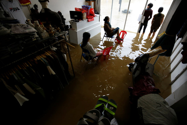 Residents sit on their flooded fashion shop after typhoon Damrey hits Vietnam in Hue city, Vietnam on November 5, 2017. A powerful typhoon that rocked Vietnam has killed dozens of people and caused extensive damage to the country's south-central region ahead of the APEC summit that will draw leaders from around the world, the government said Monday. (Photo by Reuters/Kham)