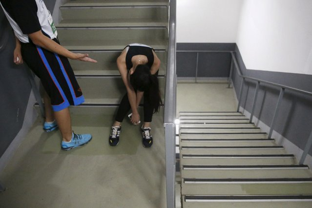 A participants encourages another exhausted participant during a vertical run event at China World Summit Wing hotel in Beijing, China, September 19, 2015. (Photo by Kim Kyung-Hoon/Reuters)