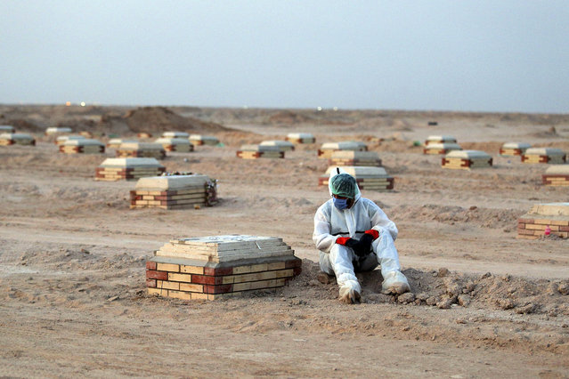An Iraqi man in a hazmat suit mourns over a tombstone at a cemetary for COVID-19 victims, 20 km from the central Iraqi holy city of Najaf, on June 10, 2020. (Photo by Ali Najafi/AFP Photo)