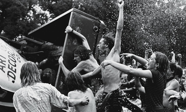 "Young demonstrators (many shirtless) shout and cheer as they overturn a truck trailer in the Reflecting Pool on the Mall facing the Washington Monument during the ""Honor America Day Smoke-In"" thrown by marijuana activists to protest the official ""Honor America Day"" ceremonies being held at the Lincoln Memorial, Washington, DC, July 4, 1970. (Photo by David Fenton/Getty Images)"