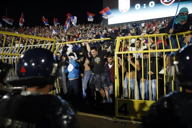 Serbian riot police try to contain Serbian supporters after a fight on the pitch broke out during the Euro 2016 Group I qualifying match between Serbia and Albania, at the Partizan stadium in Belgrade, Serbia, Tuesday, October 14, 2014. (Photo by Marko Drobnjakovic/AP Photo)