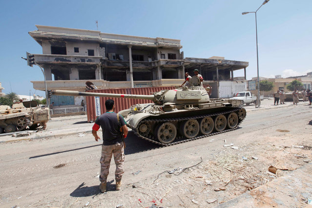Libyan forces sit atop a tank after taking up new positions as they prepare for next advance against Islamic State holdouts in Sirte, Libya August 29, 2016. (Photo by Ismail Zitouny/Reuters)