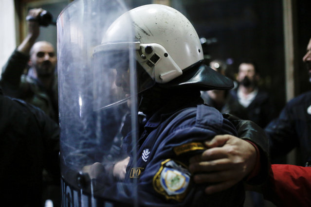 Protesters from the communist-affiliated trade union PAME try to protect a riot police officer after storming the Labour Ministry during a demonstration against changes to laws about calling strikes in Athens, Greece, December 5, 2017. (Photo by Alkis Konstantinidis/Reuters)