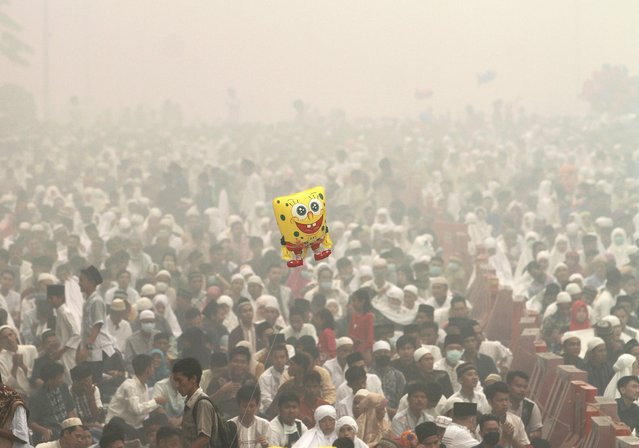 Muslim people attend an Eid al-Adha mass prayer as haze shrouds at Agung Mosque in Palembang on Indonesia Sumatra island, September 24, 2015 in this picture taken by Antara Foto. (Photo by Nova Wahyudi/Reuters/Antara Foto)