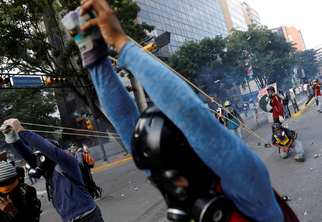 """Demonstrators use a giant slingshot while clashing with security forces during a rally against Venezuela's President Nicolas Maduro in Caracas, Venezuela, May 20, 2017. Hundreds of thousands of Venezuelans took to the streets on Saturday to mark 50 days of protests against the government of President Nicolas Maduro, with unrest gaining momentum despite a rising death toll and chaotic scenes of nighttime looting. Carlos Garcia Rawlins: """"While the days of battle in the street passed, it was evident that little by little, """"The Resistance"""", the group that was always at the forefront of opposition protests, had developed new strategies to confront the sophisticated riot control equipment of the police"""". (Photo by Carlos Garcia Rawlins/Reuters)"""
