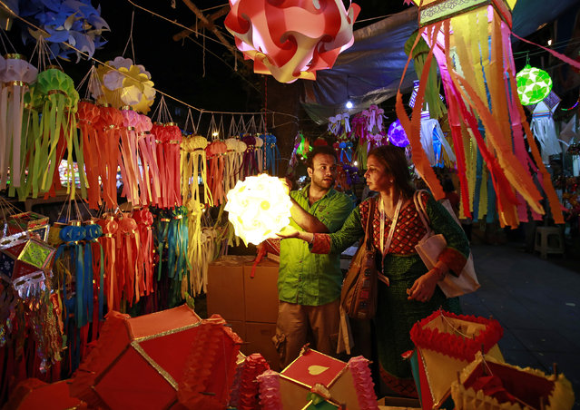 A vendor speaks to a customer at his roadside lantern stall at a Diwali market in Mumbai October 20, 2014. (Photo by Danish Siddiqui/Reuters)