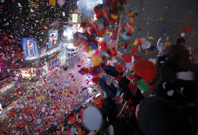 Confetti is dropped on revelers at midnight during New Year celebrations in Times Square in New York January 1, 2013. (Photo by Gary Hershorn/Reuters)