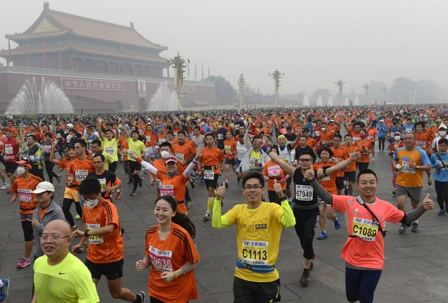 Participants run past the Tiananmen gate with a portrait of China's late leader Mao Zedong on a hazy day during the Beijing International Marathon in Beijing October 19, 2014. (Photo by Reuters/Stringer)