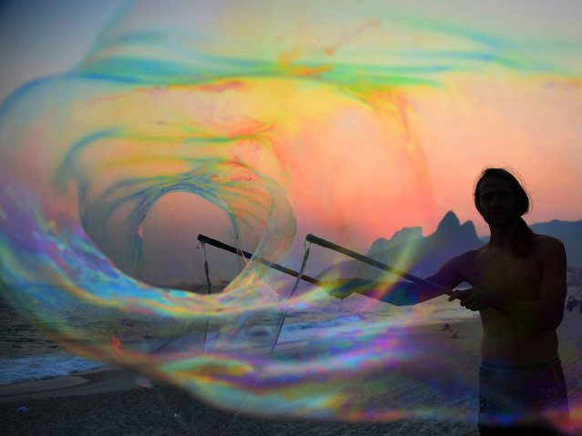 German tourist Florian plays with bubbles at sunset, in Ipanema beach in Rio de Janeiro on October 13, 2014. (Photo by Christophe Simon/AFP Photo)