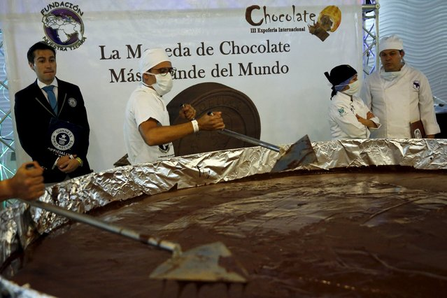 Carlos Martinez (L), a representative of the Guinness World Records, examines the cooking process of a chocolate coin during an attempt to break the Guinness World Record for the biggest chocolate coin in Caracas, Venezuela, October 1, 2015. (Photo by Carlos Garcia Rawlins/Reuters)