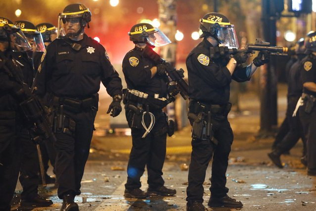 Police officers try to disperse a crowd in San Francisco, California October 29, 2014. (Photo by Stephen Lam/Reuters)