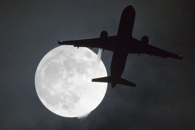 "A plane flys in front of a ""super moon"" or ""wolf moon"" on its approach to London Heathrow Airport on January 1, 2018. (Photo by Justin Tallis/AFP Photo)"