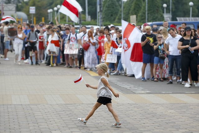 A girl walks holding a small old Belarusian national flag as activists greet and support workers leaving the Minsk Tractor Works Plant after their work shift in Minsk, Belarus, Tuesday, August 18, 2020. Workers in Belarus are joining a growing strike, turning up pressure on the country's authoritarian leader to step down after winning an election they say was rigged. (Photo by Sergei Grits/AP Photo)