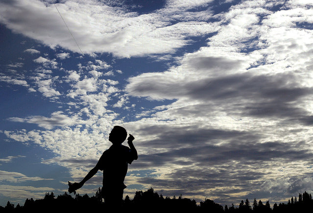 Kayden Foster,12, of Bremerton, Wash., adjusts his kite line as he flies one at Lions Park in East Bremerton on Sunday, October 19, 2014. (Photo by Larry Steagall/AP Photo/Kitsap Sun)