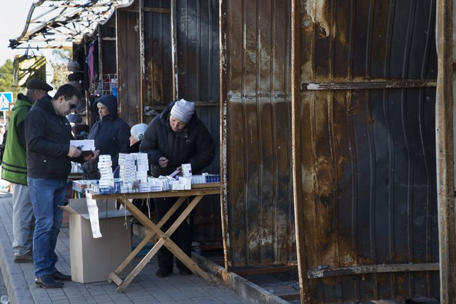 In this photo taken on Tuesday, October 28, 2014, a man buys cigarets at a bombed out street market near the train station in the town of Donetsk, eastern Ukraine. (Photo by Dmitry Lovetsky/AP Photo)