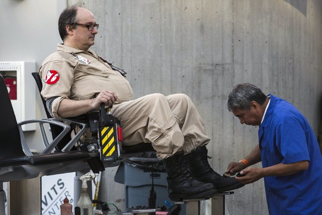 A man dressed as a Ghostbuster has his shoes shined at New York Comic Con in Manhattan, New York, October 8, 2015. (Photo by Andrew Kelly/Reuters)