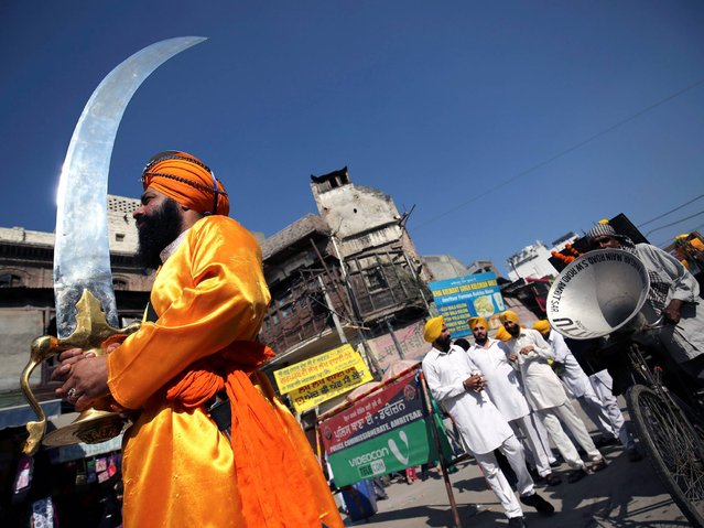 A Sikh devotee carries on over-sized religious sword during a religious procession to celebrate the birth anniversary of the first Sikh Guru or master, Sri Guru Nanak Dev Ji, the founder of Sikhism in Amritsar, India, 05 November 2014. The birth anniversary of Guru Nanak Dev Ji will be observed on 06 November. (Photo by Raminder Pal Singh/EPA)