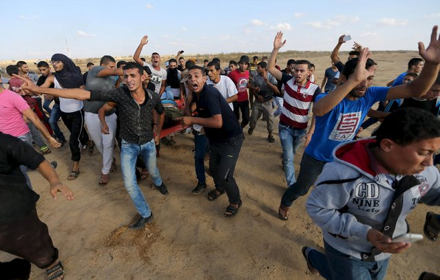 Palestinians evacuate the body of a Palestinian protester, who was shot and killed by Israeli troops during clashes, near the Israeli border fence in Khan Younis in the southern Gaza Strip October 9, 2015. Israeli troops shot dead five Palestinians in protests in Gaza on Friday and a knife-wielding Jewish man wounded four Arabs in southern Israel in a wave of violence that has fueled talk of a new uprising against Israeli occupation. (Photo by Ibraheem Abu Mustafa/Reuters)