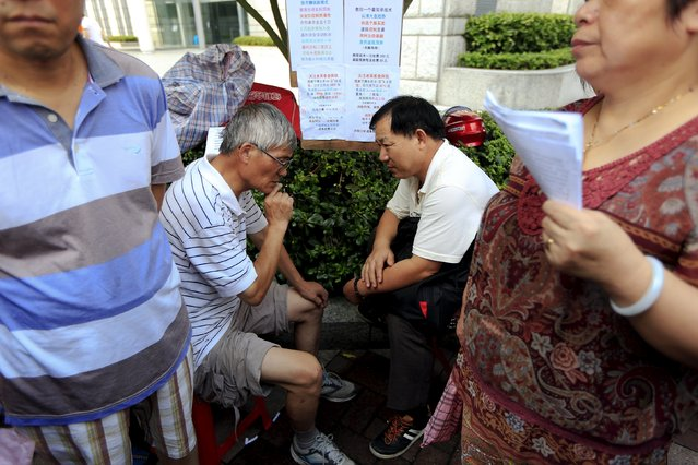 """Wu Lin'an (2nd, L) advices an investor on current trends in China's stock market during a """"street stock salon"""" in central Shanghai, China, August 29, 2015. Wu, seeing himself as a senior player in stock investment, believes and advises others that the Chinese Communist Party will save the stock market and make people rich. (Photo by Aly Song/Reuters)"""