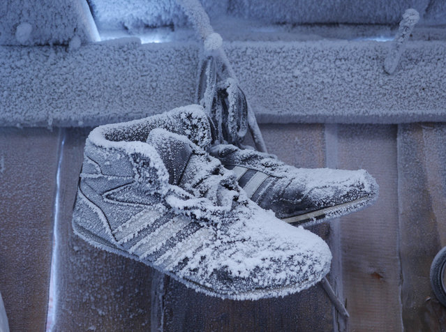 """Frozen shoes in a house in Oymyakon. Chapple says the village guesthouse he stayed in was relatively comfortable, if you used a little creativity: """"The heating pipes near my bed were sizzling hot, but the walls were icy cold. If you wriggled into just the right position between the two, you could get a relatively good night's sleep"""". Here: Summer shoes waiting out the winter in a shed in the suburbs. (Photo by Amos Chapple/Courtesy Images/RFE/RL)"""